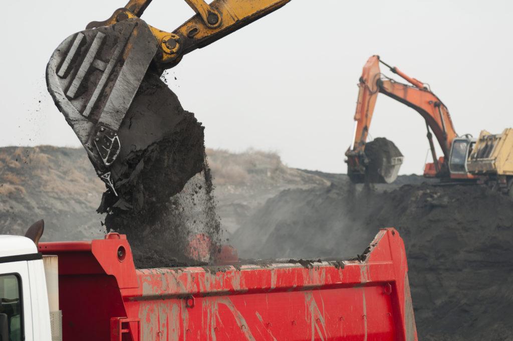 Excavator loads a dump truck