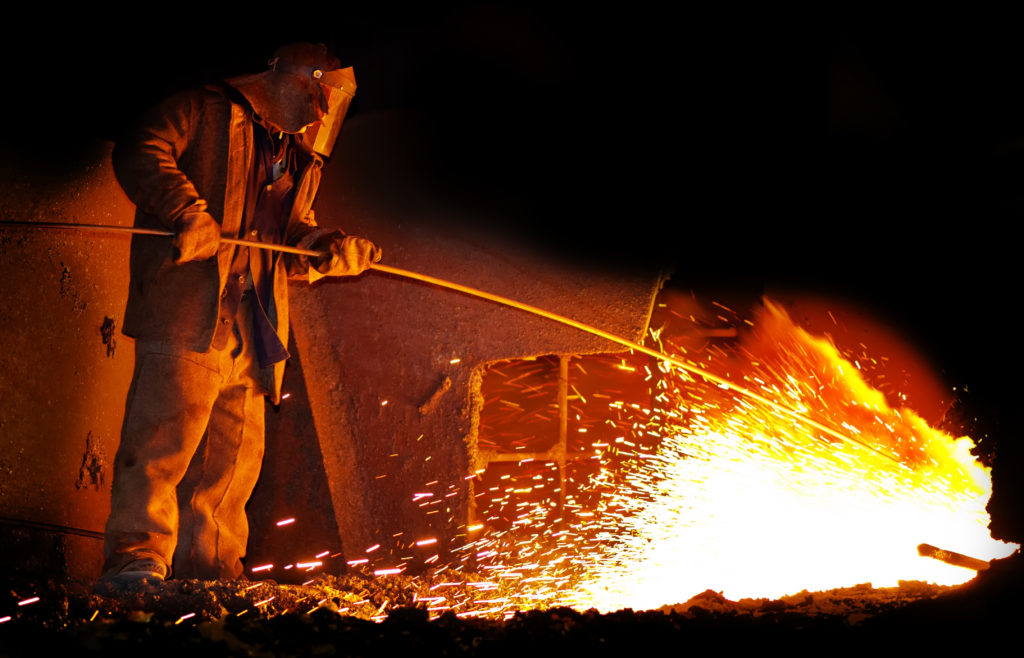 Worker standing by sparking furnace using a long tool